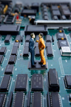 data processor: Figurines on men standing over motherboard and arguing