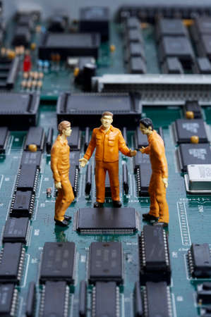 data processor: Figurines of men standing over motherboard and discussing LANG_EVOIMAGES