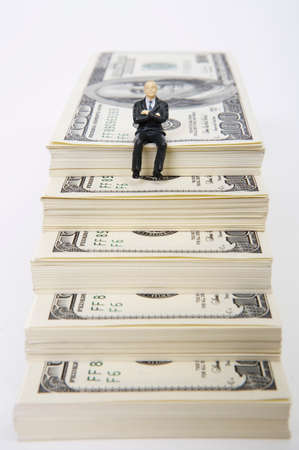 well made: Male figurine sitting on stack of dollars