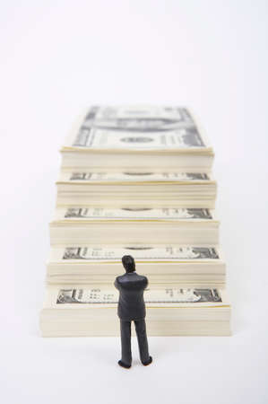 well made: Male figurine standing in front of stack of dollars LANG_EVOIMAGES
