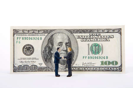 well made: Male figurines shaking hands in front of 100 dollar note LANG_EVOIMAGES