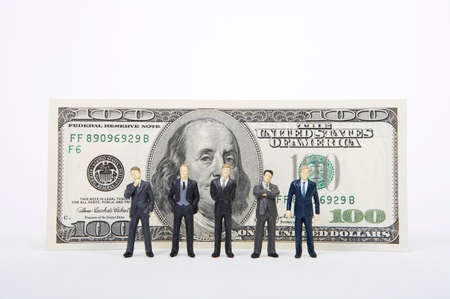 man made object: Male figurines standing in front of 100 dollar note