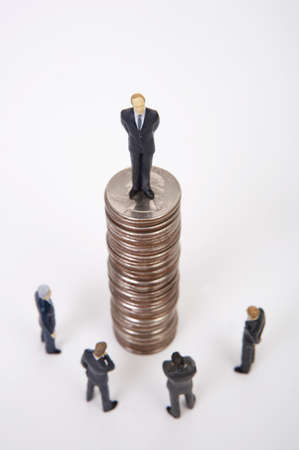 global investing: Male figurine standing on top of stacked coins