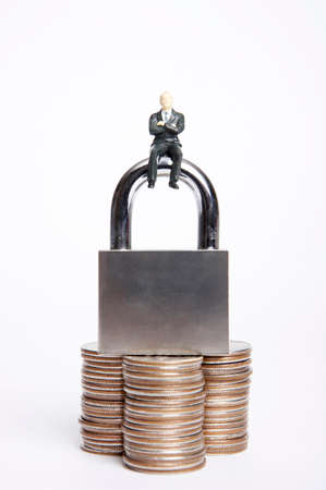 man made object: Male figurine sitting on lock with support of coins