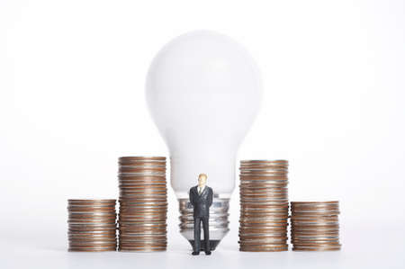 well made: Male figurine standing in front of light bulb and stack of coins