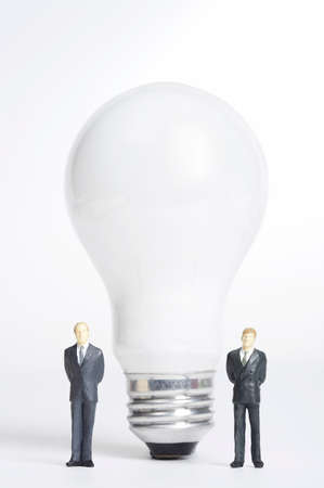 man made object: Male figurines standing on both side of electric bulb