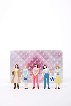 man made object: Female figurines standing in front of credit card