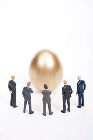 man made object: Golden egg surrounded by businessmen figurines LANG_EVOIMAGES