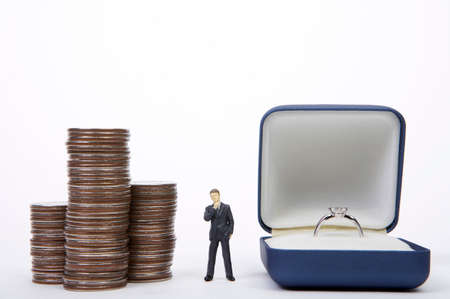 well made: Male figurine standing in middle of coins and diamond ring box LANG_EVOIMAGES