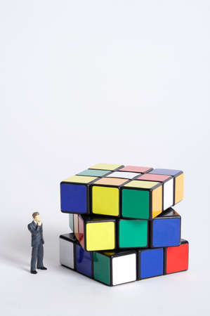 disordered: Male figurine standing in front of disordered cubic puzzle