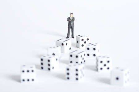 man made object: Male figurine in front of dices