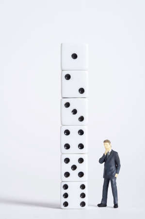 man made object: Male figurine standing in front of dice pillar