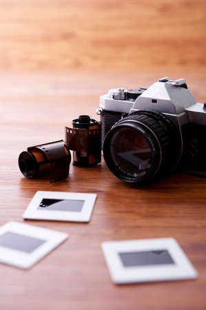 arts culture and entertainment: Camera with negatives on desk