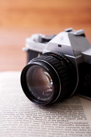 arts culture and entertainment: Close up of a camera on open book LANG_EVOIMAGES