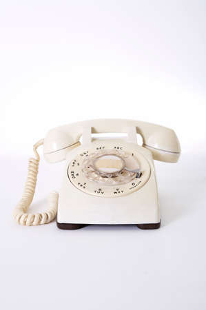 accessing: White rotary telephone on white background, close-up