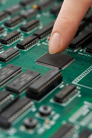 man made object: Person touching green circuit board chip LANG_EVOIMAGES