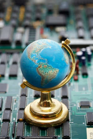 man made object: Globe on green circuit board, close up LANG_EVOIMAGES