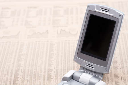 personal digital assistant: Mobile phone on a newspaper