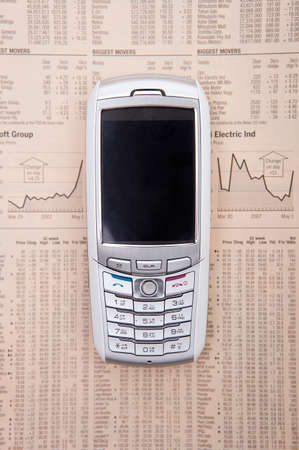 personal digital assistant: Mobile phone on a financial newspaper