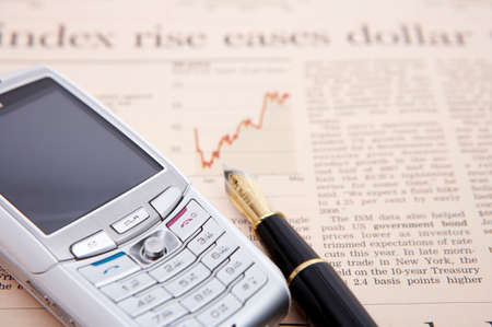 personal digital assistant: Mobile phone and pen on a financial newspaper