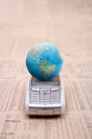 personal digital assistant: Mobile phone and globe on financial newspaper