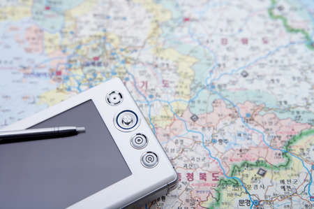 personal digital assistant: Mobile phone and stylus on world map