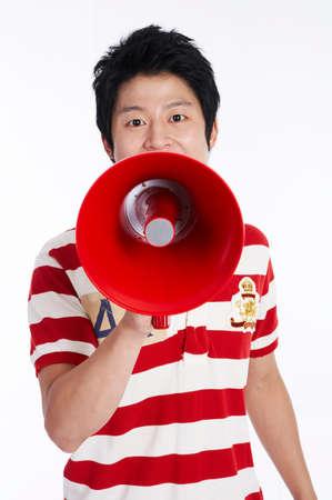 fair skin: Young man using megaphone, portrait