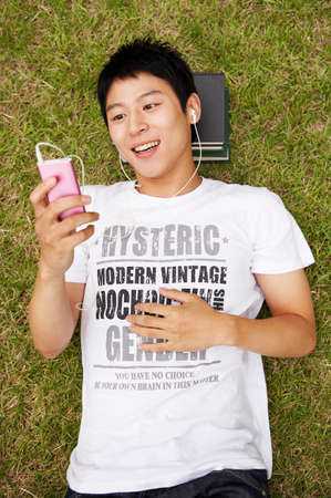 leisureliness: Young man lying on grass and listening music