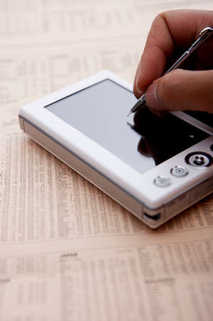 personal digital assistant: Person using mobile phone on financial newspaper