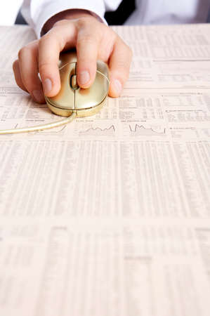 man made object: Man using computer mouse on financial newspaper