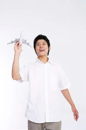 leisureliness: Young man playing with a toy airplane