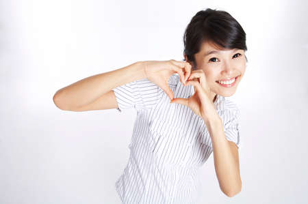 silhouette coeur: Young woman forming heart shape with hands, portrait
