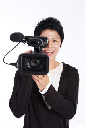 fair skin: Young man using video camera, portrait LANG_EVOIMAGES