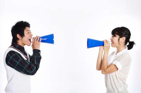mega phone: Young couple using mega phone, side by side, smiling