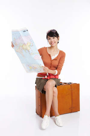 fair skin: Young woman sitting on briefcase holding world map, smiling