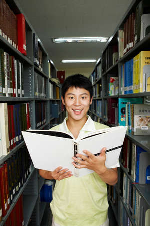 man holding book: Young man holding book in library, portrait