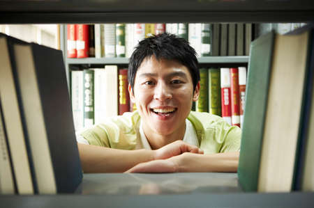 leisureliness: Young man smiling between shelves in library, portrait LANG_EVOIMAGES