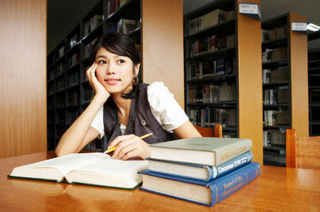 cheerfulness: Young woman studying in library