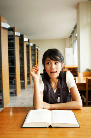 cheerfulness: Young woman studying in library, portrait