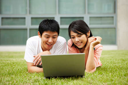 leisureliness: Young couple lying on grass, using laptop