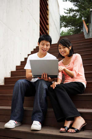 leisureliness: Young couple sitting on stairs, using laptop