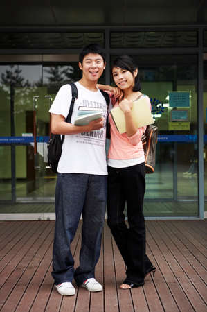 youthfulness: Young couple standing, holding books, portrait