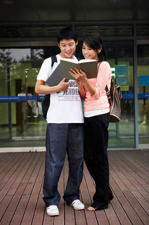 cheerfulness: Young couple reading book together