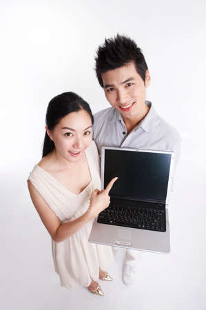 young man: Young man and woman holding laptop, portrait LANG_EVOIMAGES