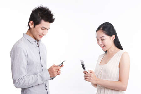 young man: Young man and woman holding mobile phone LANG_EVOIMAGES