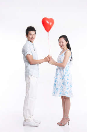 contentment: Portrait of young couple holding red balloon