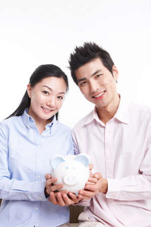 contentment: Portrait of a young couple holding piggybank