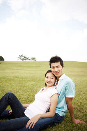 leisure wear: Young couple sitting on grassland