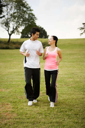 leisure wear: Young couple running on grassland