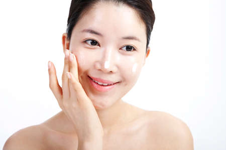 prettiness: Young woman applying face cream